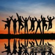 Silhouette jump team. sunset pond — Stock Photo