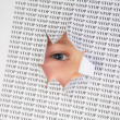 Eye looks into the hole in the sheet of paper with the printed word stop — Stock Photo #7440106
