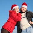 Couple against blue sky background in winter in santa claus hats — Stock Photo
