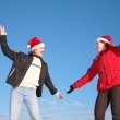 Couple dance in santa claus hats against blue sky — Stock Photo
