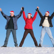 Three friends greetings on snow  in santa claus hats — Stock Photo