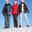 Three friends stand on snow in santa claus hats — Stock Photo