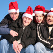 Four friends against blue sky in santa claus hats — Stock Photo
