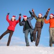 Stock Photo: Four friends jump on top of snow hill in santa claus hats