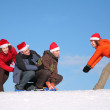 One woman pull two men on sled, other woman push them — Stock Photo #7440728