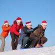 Two girls push two men on sled — Stock Photo #7440734