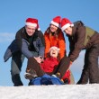 Three friends push girl on sled — Stock Photo #7440737
