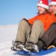 Man and woman in santa claus hats ride on sled — Lizenzfreies Foto