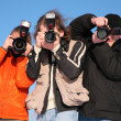 Stock Photo: Three photographers against blue sky