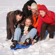 Group of friends push another one on plastic sled — Stock Photo #7440764