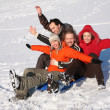 Stock Photo: Group of friends sit on plastic sled on snow