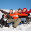 Group of friends sit on plastic sled on snow 2 — Stock Photo