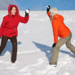Two young women play to snowballs — 图库照片