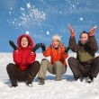 Stock Photo: Three friends sit on snow and throw snows