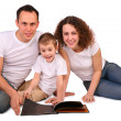 Family sits and reads magazine — Stock Photo