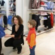 Mother with children in clothing shop — Stock Photo