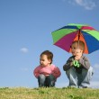 Children on meadow with umbrella — Stock Photo #7441354