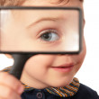Smiling child looks through magnifier — Stock Photo #7441495