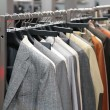Clothes on racks in shop - Stockfoto