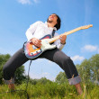 Young man plays on guitar on grass — Stock Photo #7441941