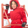 Pretty woman on metallic ladder in winter — Stock Photo