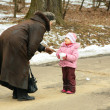Little girl with snowball speaks with woman - Stockfoto