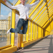 Stock Photo: Young mjumps on footbridge