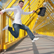 Stock Photo: Young mjumps with bag on footbridge