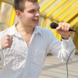 Stock Photo: Young mwith microphone on footbridge