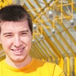 Young smiling man in yellow shirt on footbridge — Stock Photo