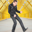 Stock Photo: Guy allegorize play on guitar on footbridge
