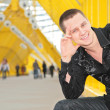 Stock Photo: Smiling guy sits on yellow footbridge