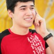 Stock Photo: Young mtalks by cell phone on yellow footbridge