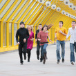 Group of young friends runs on yellow footbridge — Stock Photo