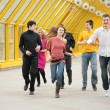 Group of friends runs on footbridge — Stock Photo