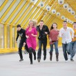 Group of friends runs on yellow footbridge — Stock Photo