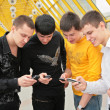 Group of young men with cell phones — Stockfoto
