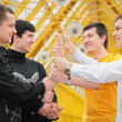 Group of young men make piramid from hands - Photo