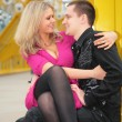 Blonde sits on boys knees on yellow footbridge — 图库照片