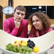 Stock Photo: Young couple on kitchen and vase with fruits