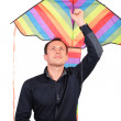 Stock Photo: Man holds kite above head