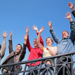 Group of stand with hands lifted in greeting — Stock Photo