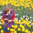 Children embrace each other on  field of tulips — Stock Photo