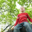 Boy sits on tree - Stock Photo