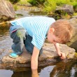Boy has lowered  hand in  stream — Stock Photo