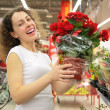 Young woman holds pot with rose in shop — Stock Photo