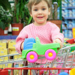 Child in shoppingcart with toy car — Stock Photo