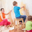Children help mother remove old wallpapers — Stock Photo