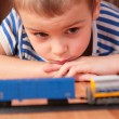 Boy looks at toy railroad — Stok fotoğraf