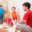 Family makes interruption in  removal of  old of  wallpapers - Stockfoto